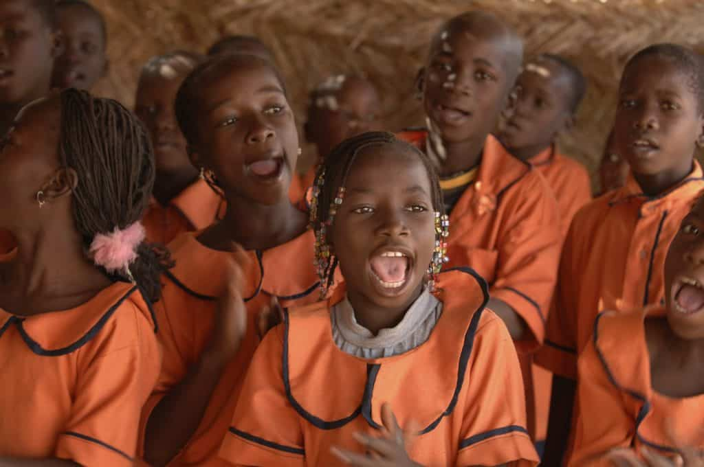 Children in orange uniforms singing and clapping