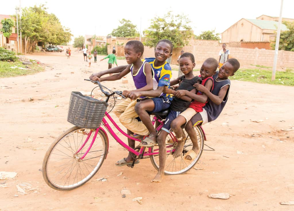 Hopeful, dignified children, in the context of their homes and neighborhoods. A group of boys, friends, buddies, children, youth, five boys pile all on top of a bicycle, bike, transportation, on a dirt road in their neighborhood street. The bike has a gray woven basket on it and the boys are smiling together.