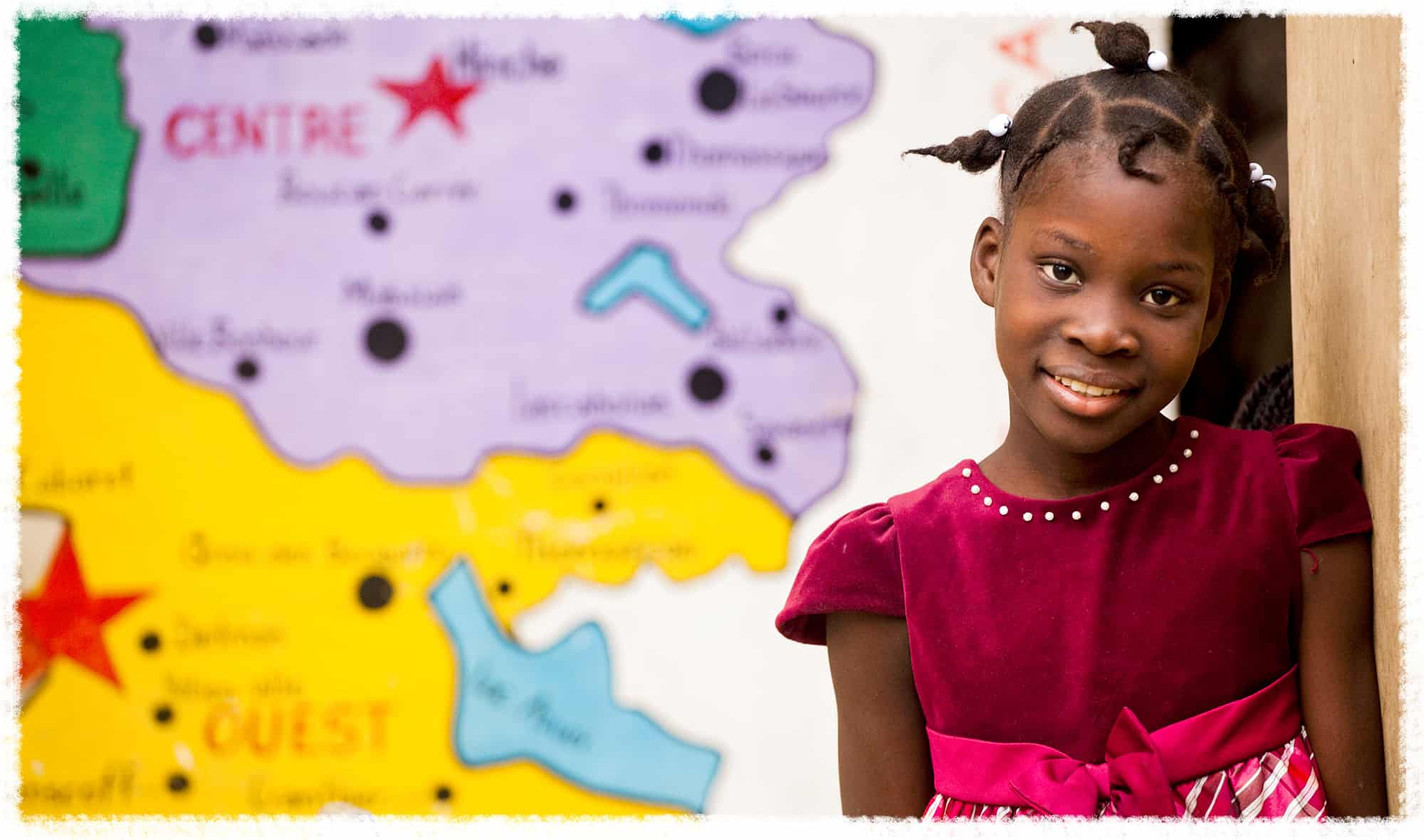 A young girl stands next to a map in her classroom in Haiti