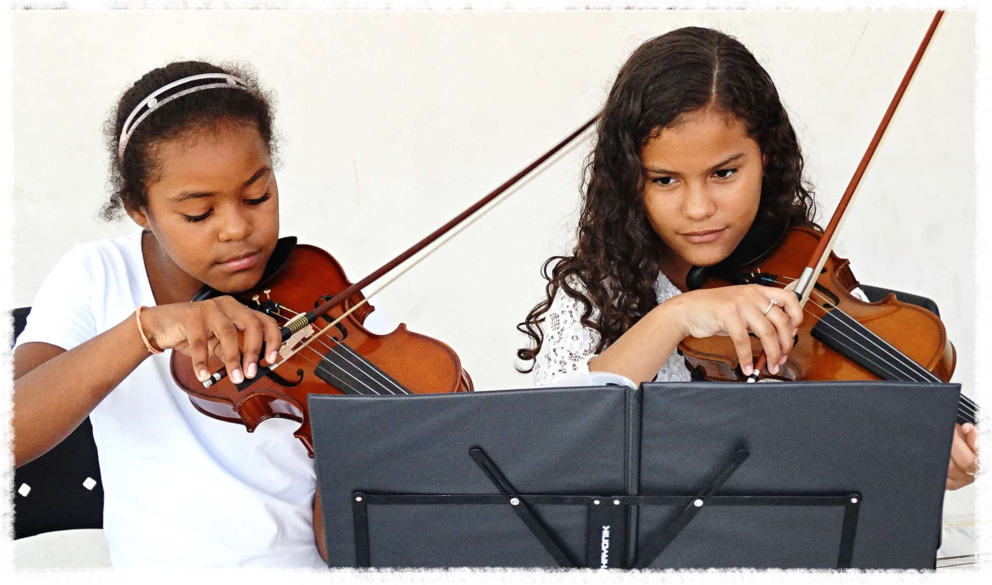 Two girls play violin together at their Compassion center in Brazil.