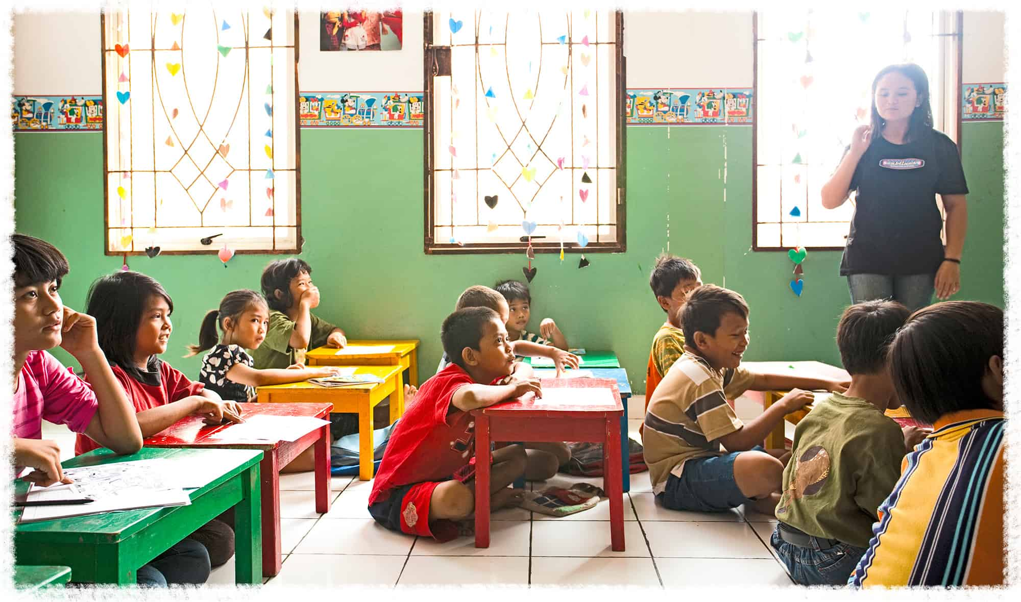 Students listen to their teacher in their classroom in Indonesia.