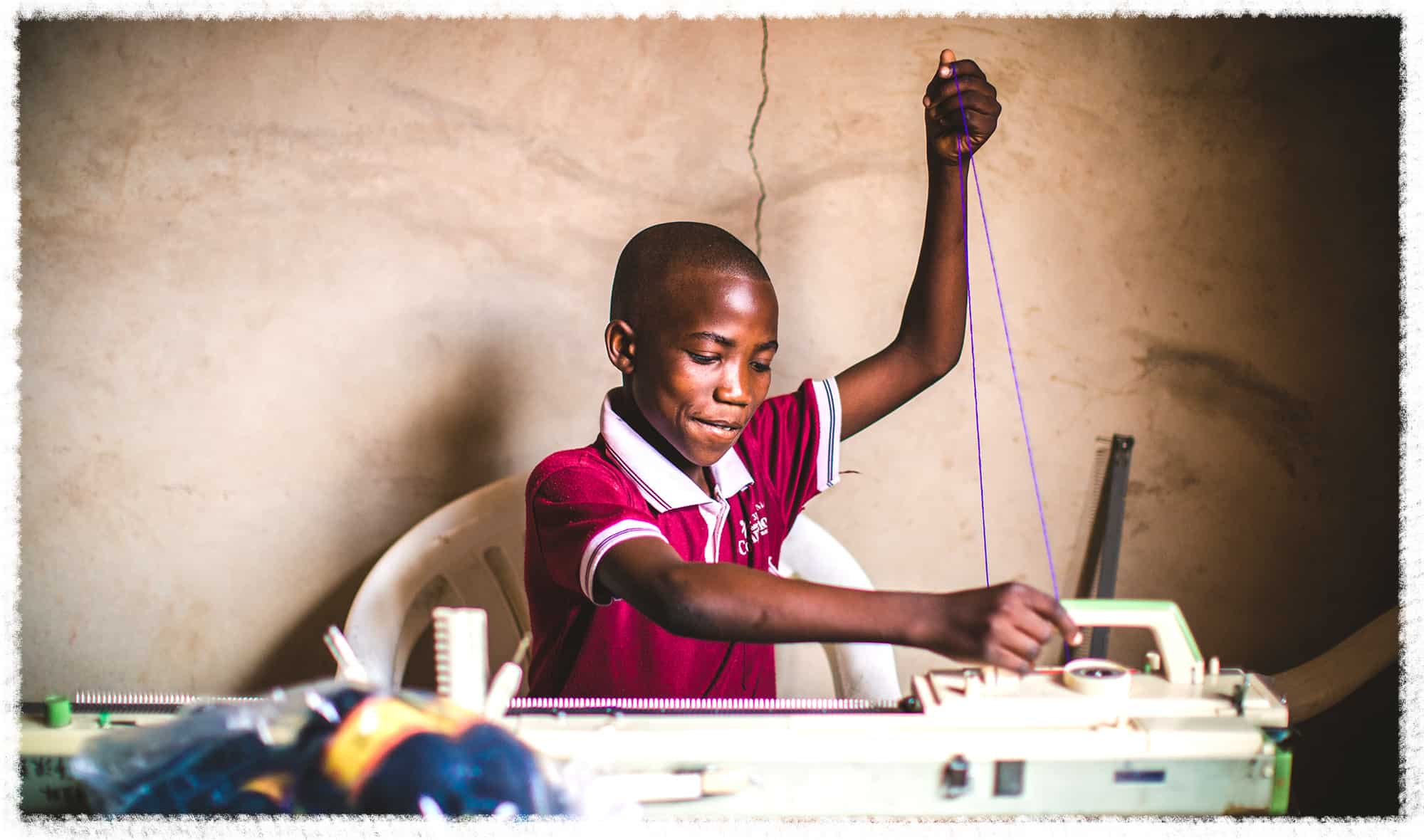 A Tanzanian student is taking a textiles class at his Compassion center.
