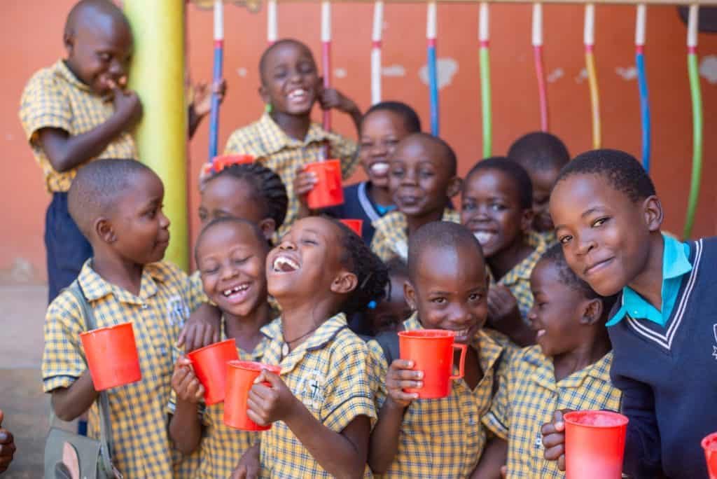 These kids in Uganda are enjoying a snack at their Compassion center.